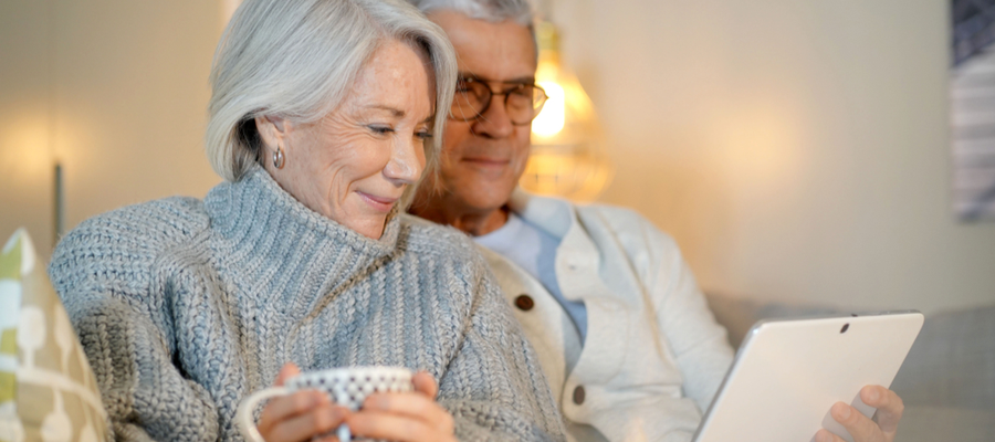 An older couple sitting on a couch smiling and looking at a device