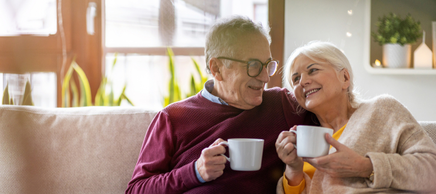 An older couple sitting on the couch holdings coffee cups smiling at each other