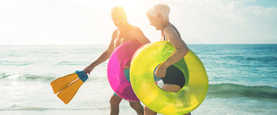 An older couple in their swimsuits holding bright coloured floating devices and flippers on the beach by the ocean