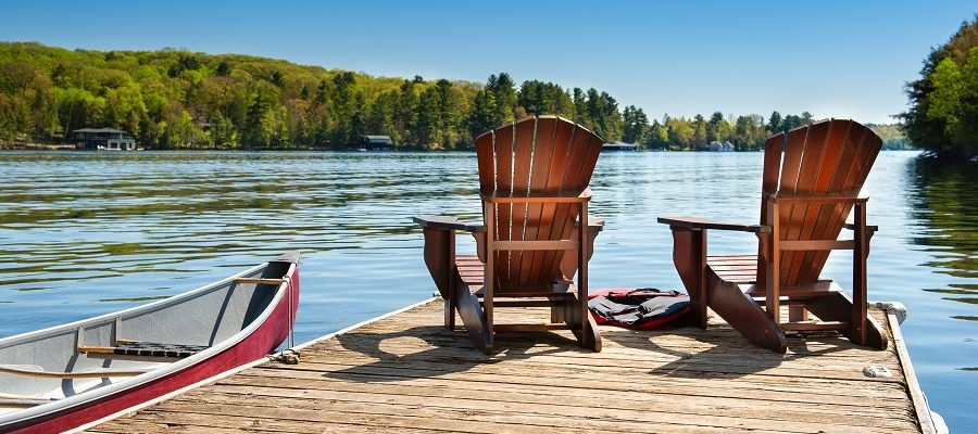 view of the lake and dock with two Muskoka chairs and a canoe
