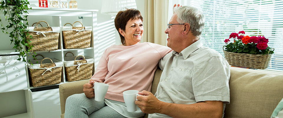 An older couple smiling at each other on the couch each holding a cup of coffee
