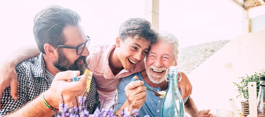 A teenage boy hugging his father and grandfather while eating outside