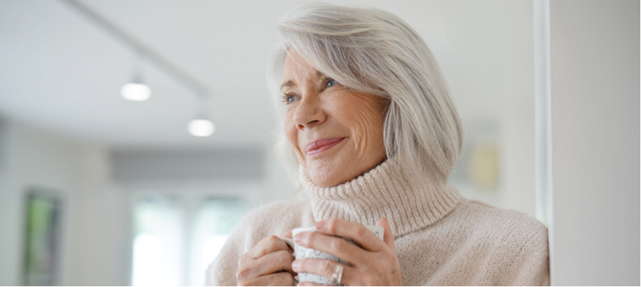 An older woman wearing a white turtleneck sweater holding a mug looking off in the distance