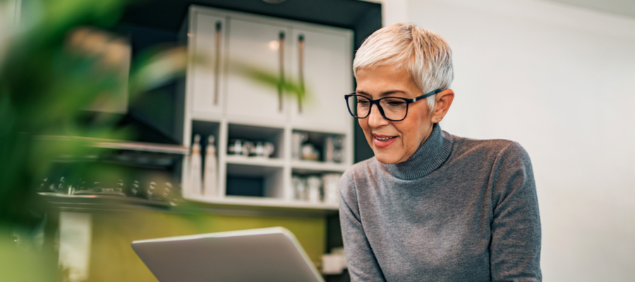 An older woman with short hair and glasses smiling and looking down at her laptop