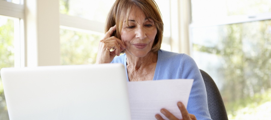 An older woman at a laptop looking at a document