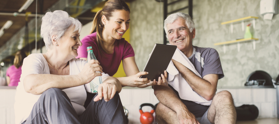 A woman showing her tablet with an older couple in exercise clothes