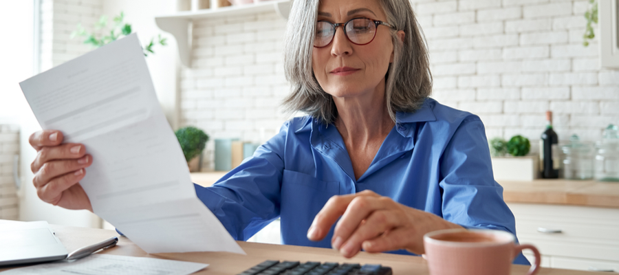 Senior mature business woman holding paper bill using calculator, old lady managing account finance, calculating money budget tax, planning banking loan debt pension payment sit at home kitchen
