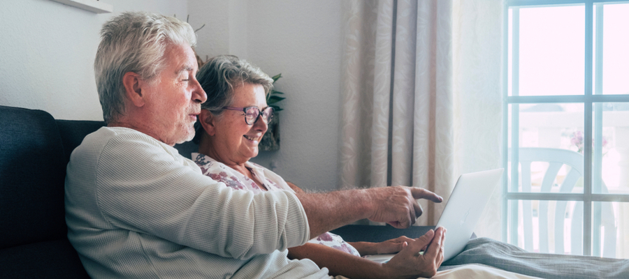 An older couple sitting together on a couch looking at a laptop