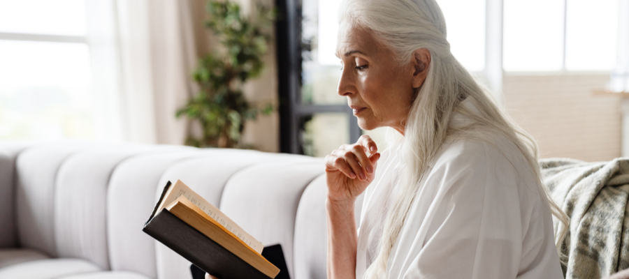 Older woman with long hair reading a book on her couch