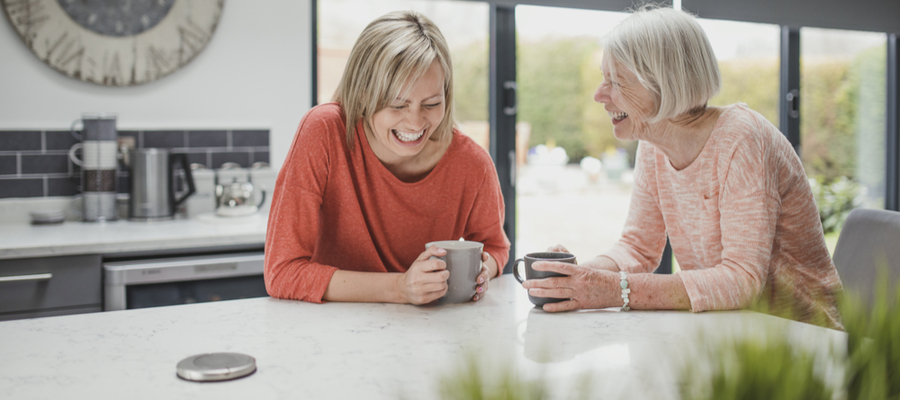 Two ladies laughing together at the kitchen counter holding coffee cups