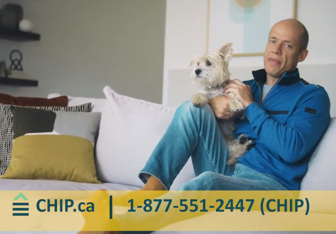 Kurt Browning holding a dog on a couch