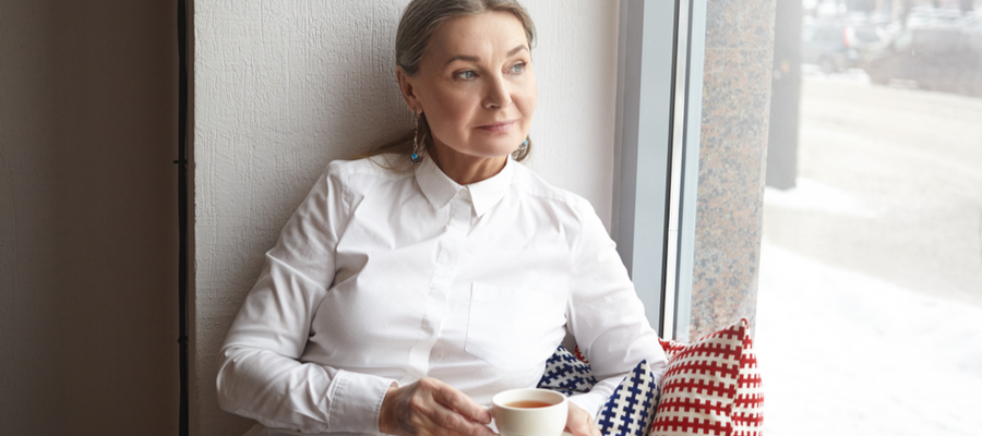 A woman sitting by a window holding a cup of tea looking out the window