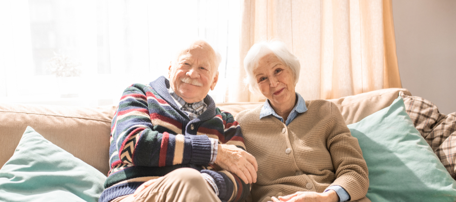 An older couple sitting on a couch smiling at the camera