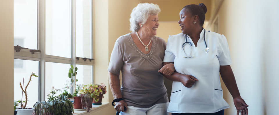 An older woman walking with a cane talking happily with a caregiver