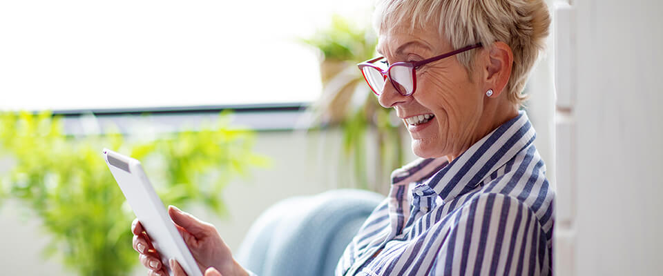 An older woman wearing red glasses happily looking at her tablet out by her balconey