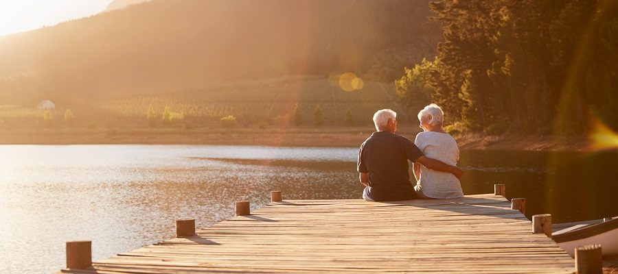 A view of an older couple sitting on the edge of dock by the lake
