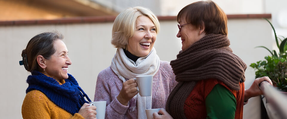 Three women standing outside smiling and talking holding coffee cups