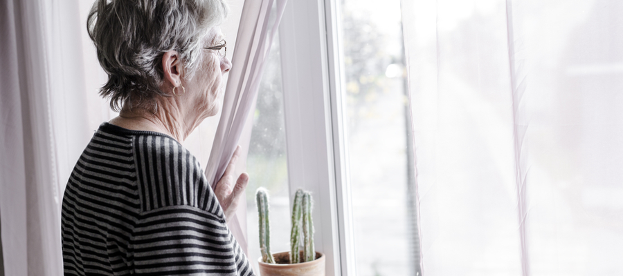 An older woman standing by the window holding the curtain aside to look out