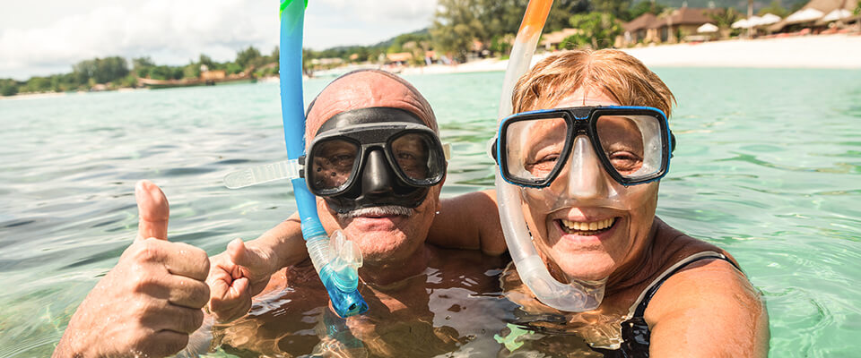 An older couple swimming in the ocean wearing snorkel goggles