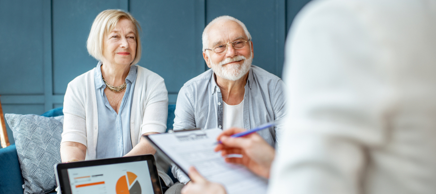 An older couple sitting with a person taking their information on a clipboard
