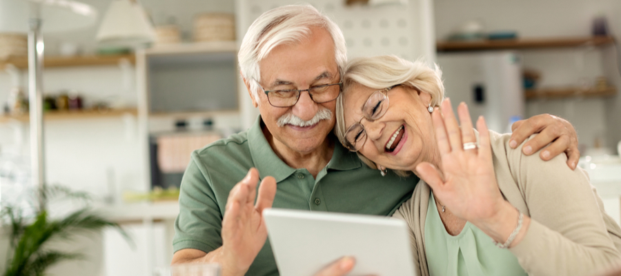 An older couple waving hi and smiling and holding a tablet