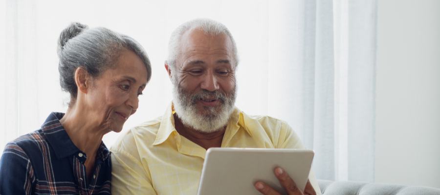 Older African couple looking at tablet together