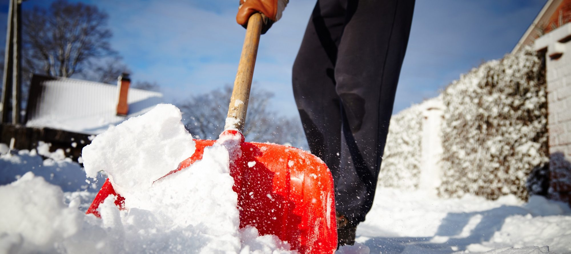 Ground level view of someone shoveling snow with a red shovel