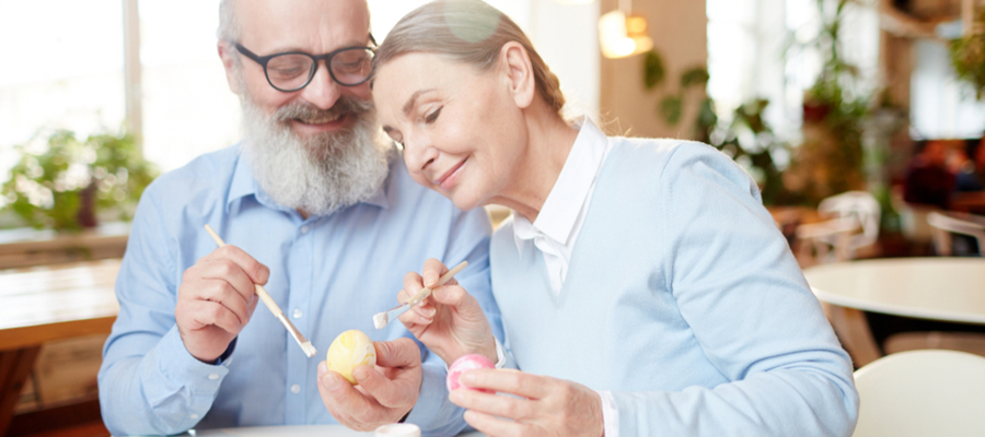 Older couple painting eggs for Easter with paintbrushes
