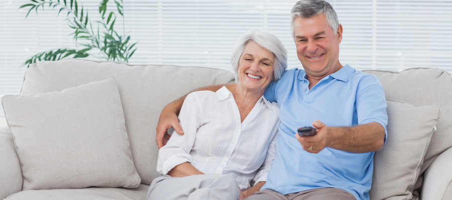 Happy older couple sitting on the couch watching TV
