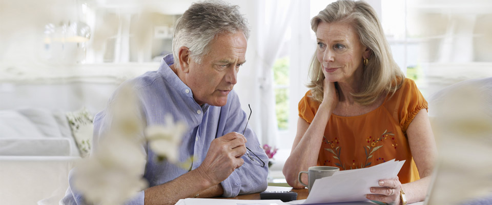 A senior couple discussing how they can plan ahead to lead a stress free retirement life.