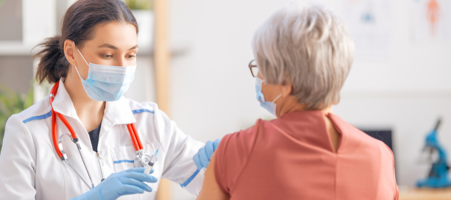 Doctor giving senior woman second dose vaccine for Covid virus