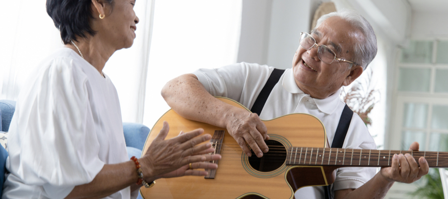 Elderly couple enjoying playing guitar