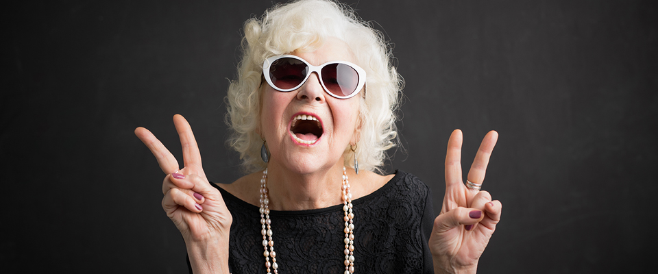 Fashion grandmother wearing white sunglasses, pearls and a black dress