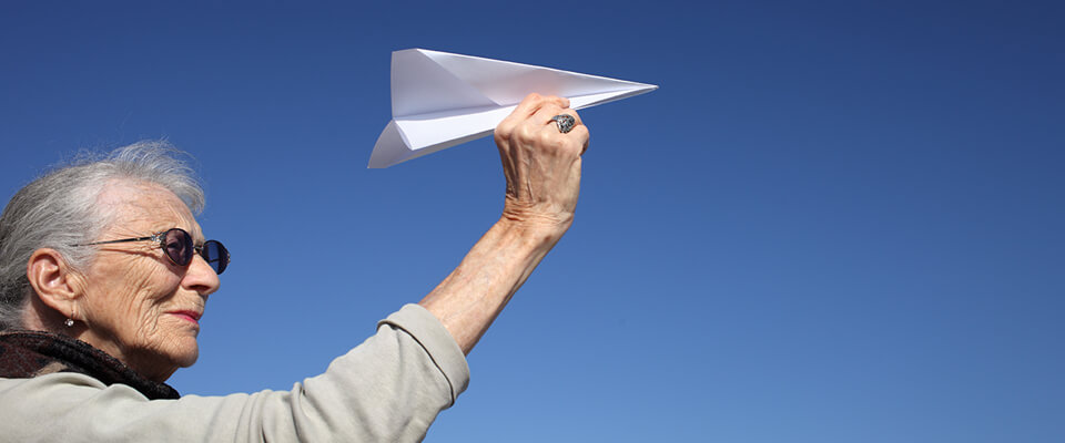 An older woman holding a paper airplane