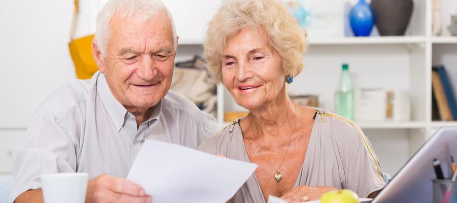 Happy Senior Spouses looking at Bills on Laptop
