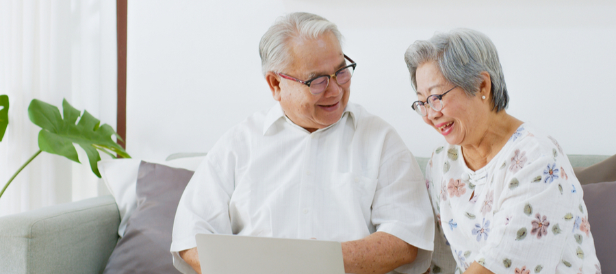 Senior Asian couple filling out a Guaranteed Income Supplement (GIS)