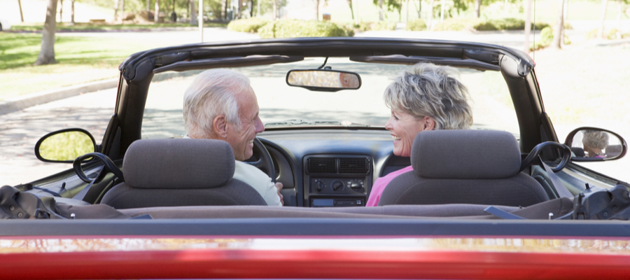 Senior couple sitting in a convertible car smiling together