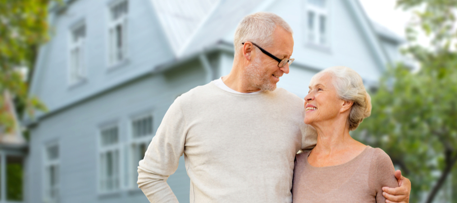 senior couple hugging in front of home