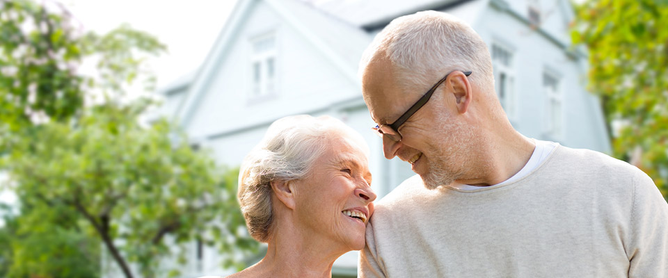 Canadian senior couple smiling and happy about retaining their home after taking a home equity loan.