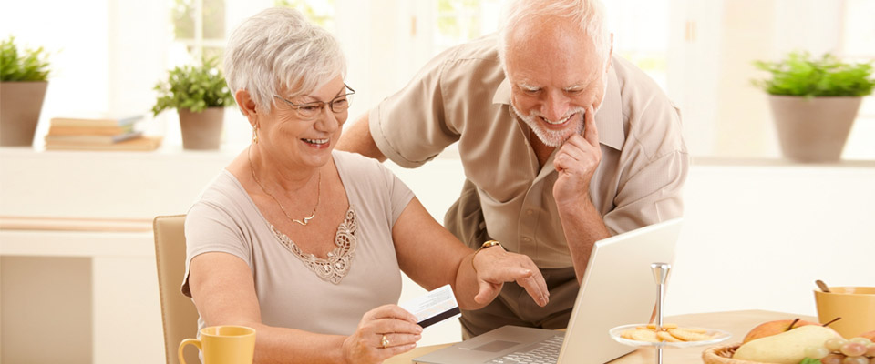 Senior couple reading information on how to secure a reverse mortgage in Canada on a laptop and smiling as they have information about how a CHIP Reverse Mortgage can help them retain their home.