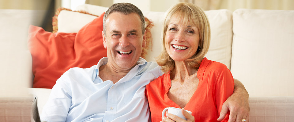 Senior couple relaxing in their living room, satisfied that they used the funds from their reverse mortgage in Canada fruitfully.