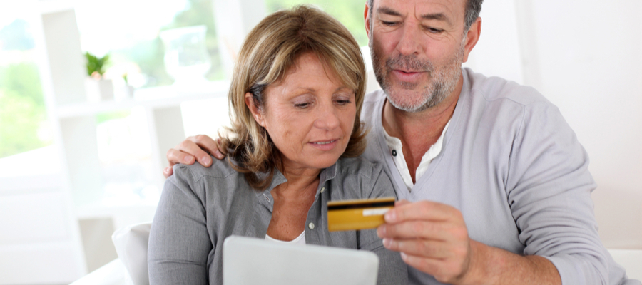 Middle aged couple using a credit card