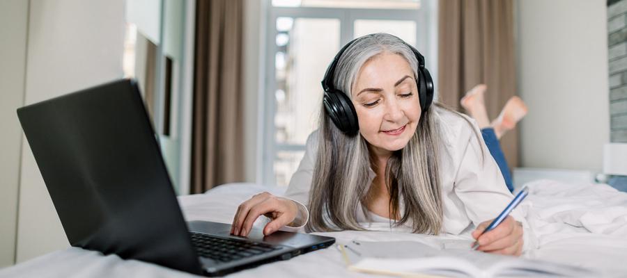 senior-woman-writing-notes-while-working-on-laptop