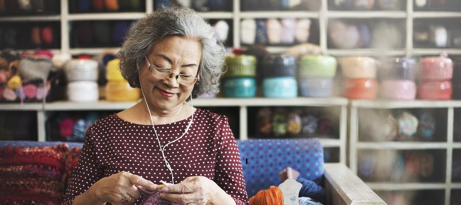 An older woman knitting and wearing headphones sitting on a couch