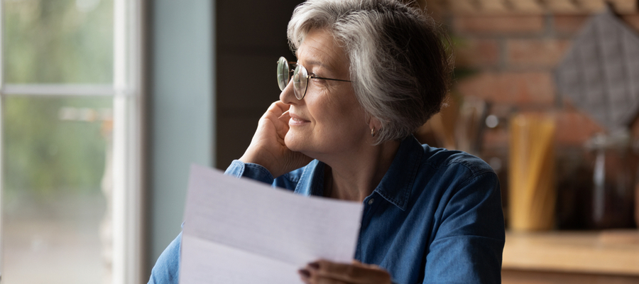 Thoughtful middle aged senior woman reviewing inheritance tax document